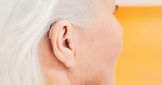 Uho s slušnim aparatom, fotografirano od zadaj